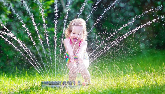 little girl plays at a sprinkler on turf