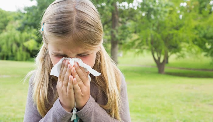 Girl blows her nose due to grass allergy