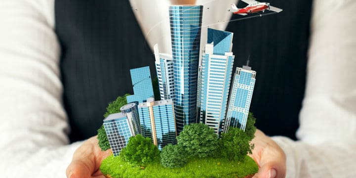 small model of garden and skyscrapers in a woman's hands