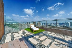 A rooftop with a Jacuzzi and a patch of lawn