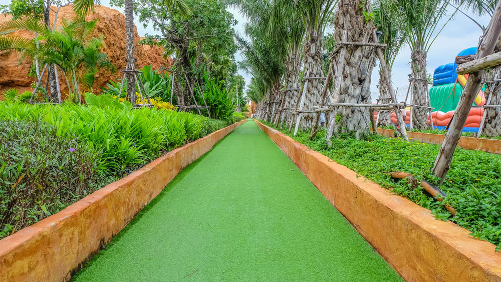 Green grass or artificial turf walkway with the garden in the park